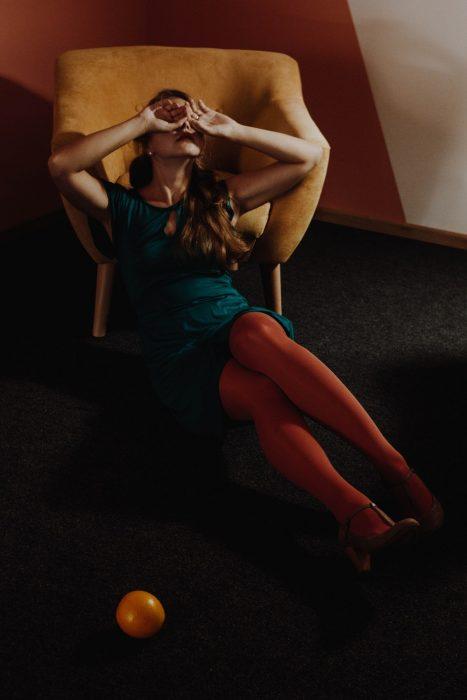 Chica con medias naranjas, sueter verde, sentada en un sofá amarillo, cubriendo sus ojoso son las palmas de sus manos cerradas en puño