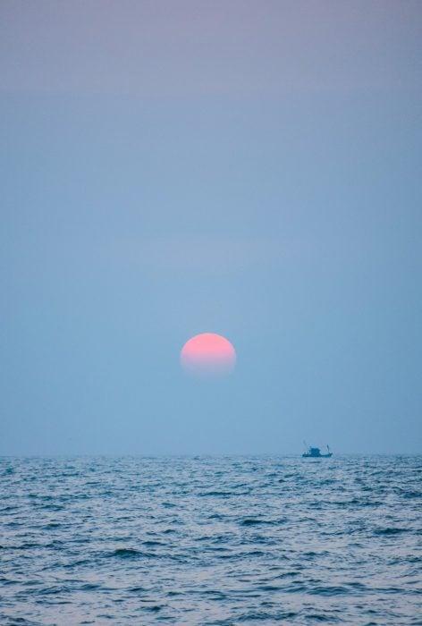 Luna Rosa a medio tardecer sobre la costa del mar