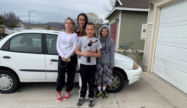 Hijo le regala un auto Toyota blanco a su mamá, familia posa en la calle frente al carro