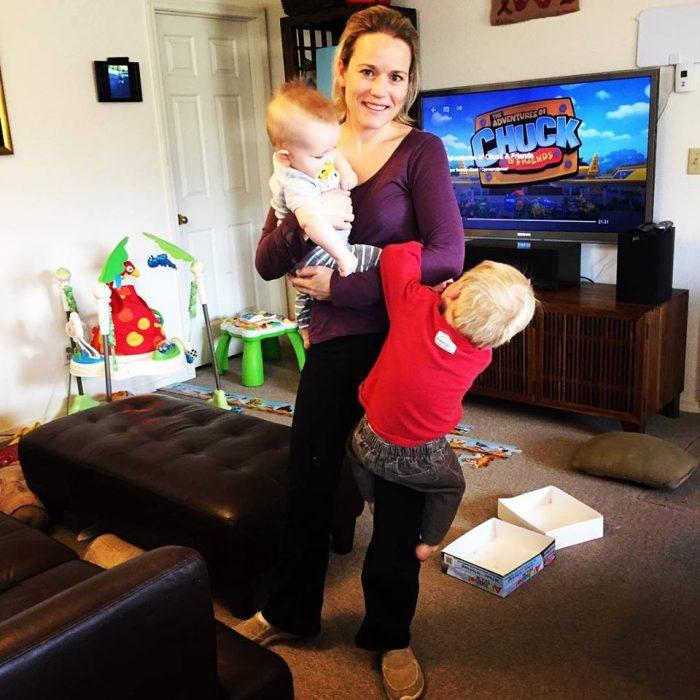 Celeste Erlach: Carta de esposa exhausta a su esposo; mamá cargando a dos niños en un cuarto con juguetes y la televisión en un canal para infantil