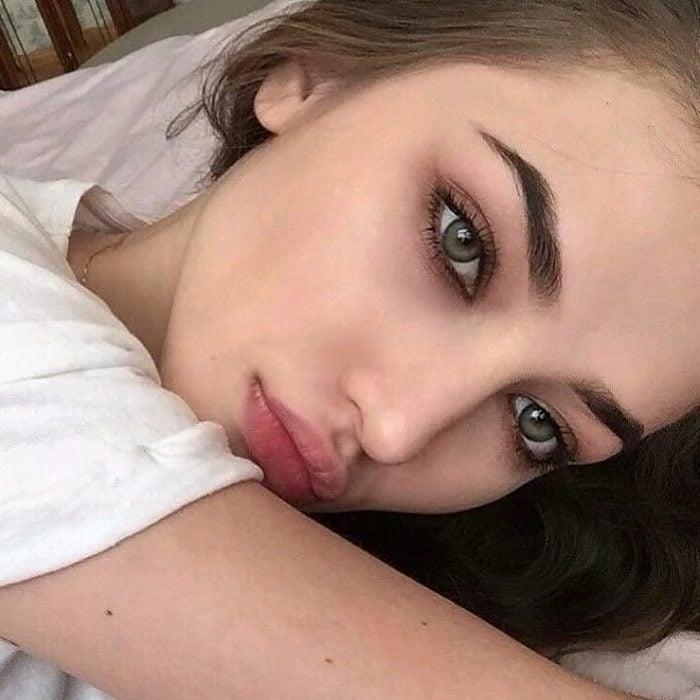 Chica recostada en una cama mirando hacia el frente para mostrar sus ojos verdes