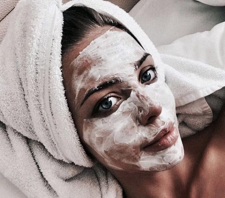 Chica recostada sobre su cama llevando mascarilla facial para limpiar la piel
