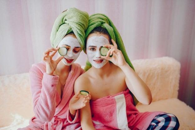 Amigas usando mascarillas refrescantes y rodajas de pepino sobre los ojos