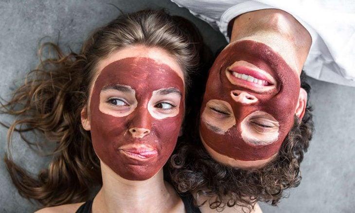 Pareja de novios recostados sobre el piso usando mascarilla de arcilla roja para las impurezas
