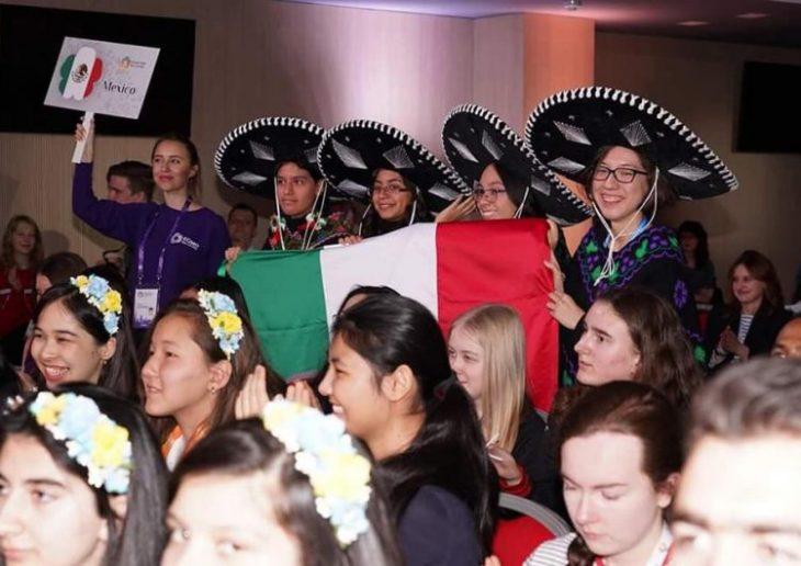 Ana Paula Jiménez, Nuria Sydykova Méndez y Karla Rebeca Munguía Romero usando sombreros charros con detalles plateados sosteniendo una bandera mexicana durante las olimpiadas europeas femenil en matemáticas