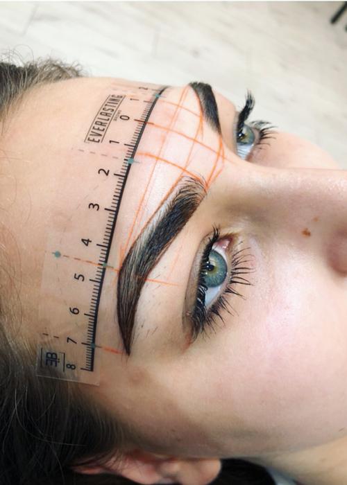 Chica de ojos verdes con cejas pobladas y lunar en la nariz, con medidas dibujadas en el rostro para microblading