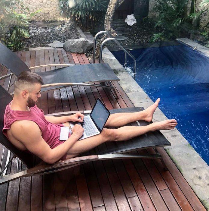 Matthew Lepre sentado con su computadora en su regazo cerca de la alberca