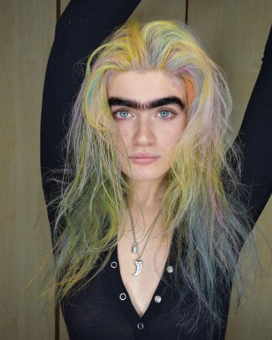 Modelo británica Sophia Hadjipanteli con uniceja, chica de cejas pobladas negras, ojos verdes, sin maquillaje, cabello largo de colores amarillo, anaranjado, lila y verde