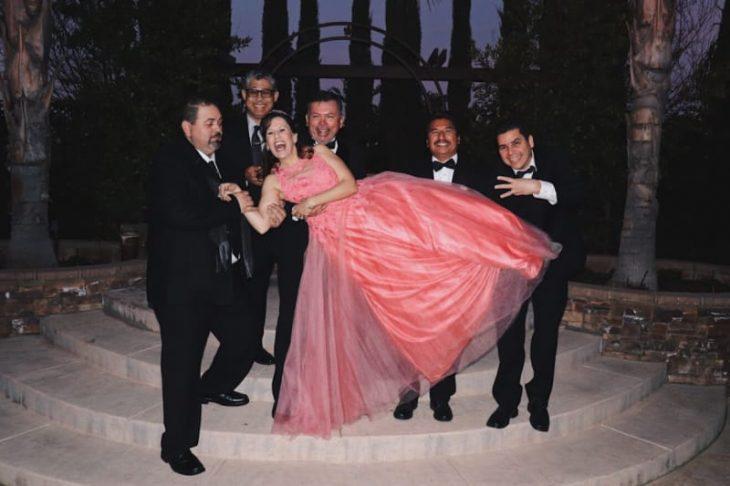 Grupo de cinco hombres con trasjes sastre en negro, formados en una fila frente a unas escaleras se asfalto, cargando a una mujer con vestido ampon en color coral quien ríe atemorizada