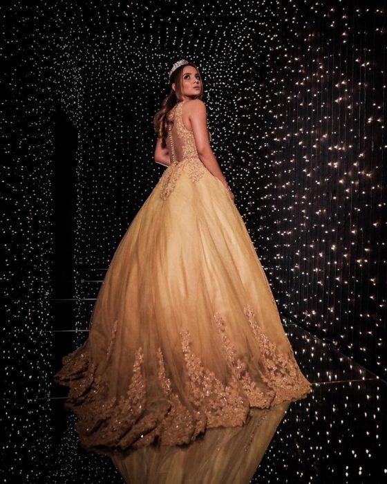Chica usando vestido dorado posando en un cuarto cubierto con luces doradas, mirando de lado sobre su hombro, llevando tiara de piedras doradas, con peinado rizado