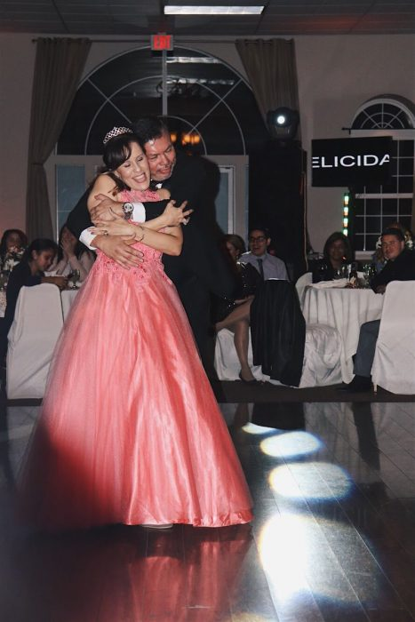 Hombre abrazando por la espalda a una mujer en una fiesta de XV años, después de bailar el vals, mujer llevando vestido color coral , ampon , tiara, hombre con traje sastre en tono negro y corbatín