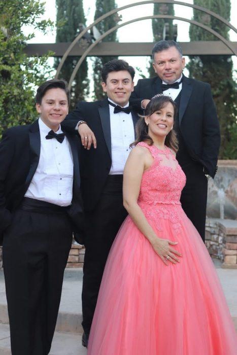 Familia posando frente a unas escaleras de asfalto para una foto del recuerdo, mujer usando vestido de quinceañera color coral, llevando tiara plateada, con el brazo en la cintura, hombres llevando traje sastre en colore negro con corbatín, con el brazo uno encima del hombro del otro