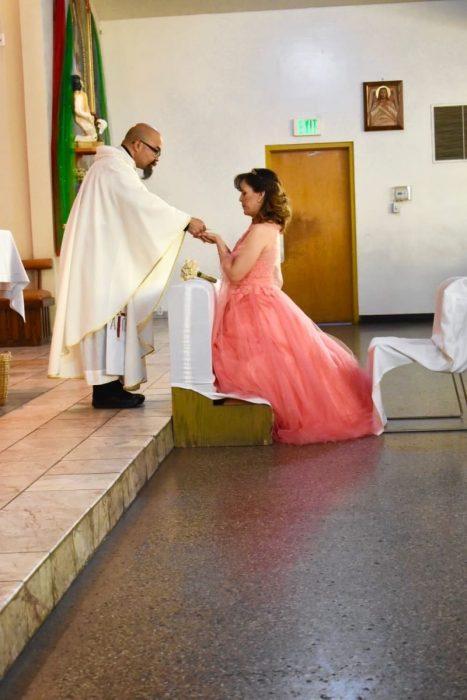 Mujer dentro de una iglesia, hincada frente a un sacerdote, tomando las manos de él, mirando al piso, hombre con sotan, agachado, entregando una ostia a una mujer durante una misa de celebración de xv años