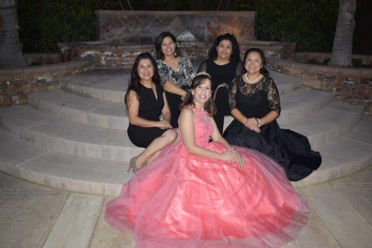 grupo de mujeres sentadas al filo de unas escaleras de aslfato, posando para una foto de recuerdo de una fiesta de xv años, son la spiernas cruzadas, llevando vestidos de color negro, con detalles en canaje, mujer al centro llevando vestido ampon de color coral estilo quinceañera