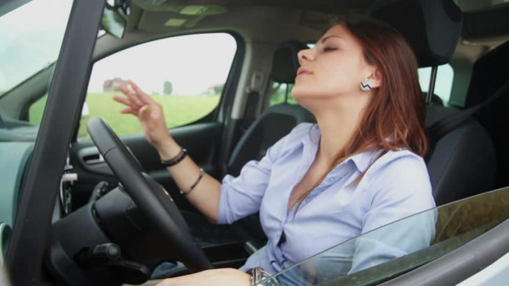 Mujer pelirroja dentro de un auto sin cinturón de seguridad.
