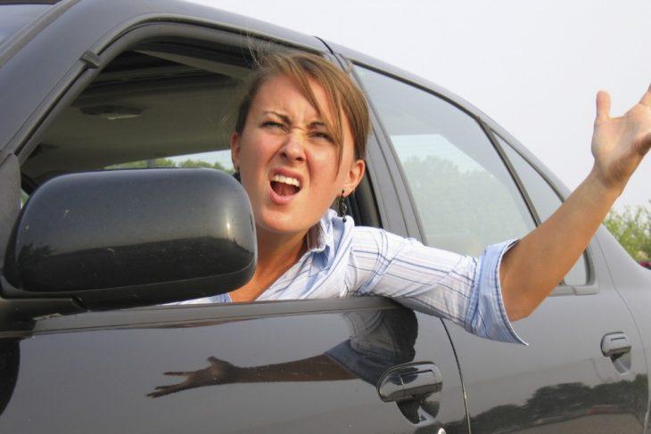 Mujer dentro de un auto con la cabeza y el brazo afuera reclamando enojada