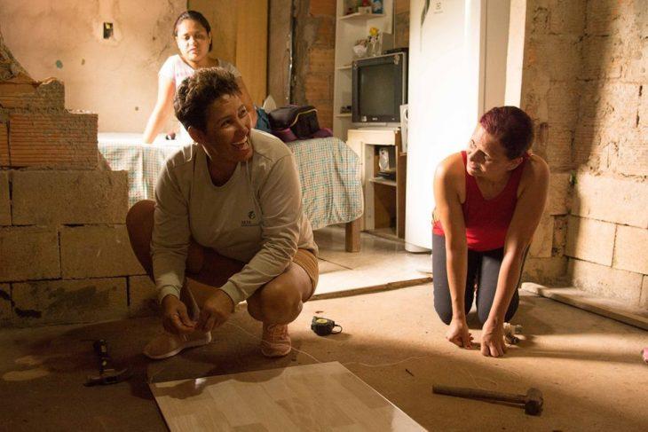 Mujeres brasileñas aprenden técnicas de arquitectura para construir sus propias casas, mujeres riendo mientras colocan el piso de su hogar