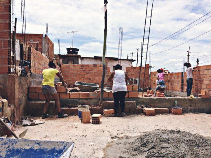 Mujeres brasileñas aprenden técnicas de arquitectura para construir sus propias casas, grupo de mujeres poniendo ladrillos