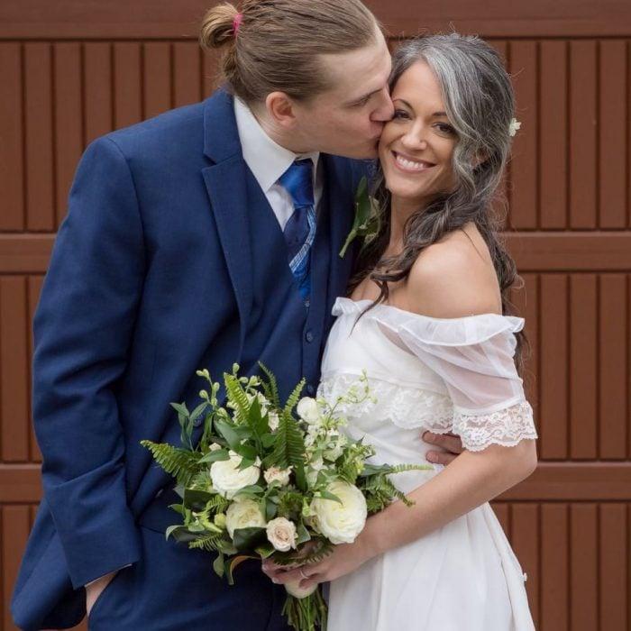 Pareja de esposos abrazados, mujer con cabello canoso, vestido blanco de novia y ramo de flores blancas, hombre de traje azul con cabello rubio, largo agarrado en una coleta