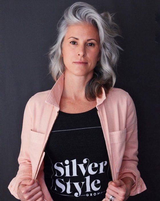Mujer con canas con una blusa negra que dice Silver Style y una chamarra de mezclilla rosa