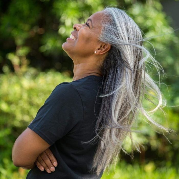 Mujer afroamericana posando de perfil y sonriendo, cabello largo, lacio y con canas