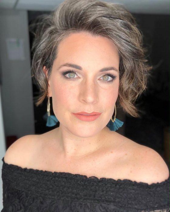 Mujer de ojos verde claros, con cabello corto, ondulado y canoso