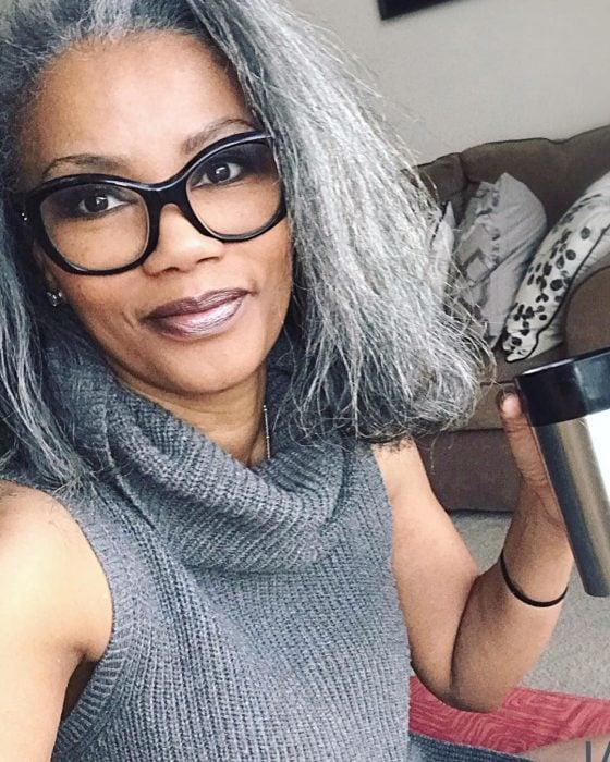 Mujer morena, afroamericana usando lentes y bebiendo café de un termo, blusa tejida gris y cabello corto con canas