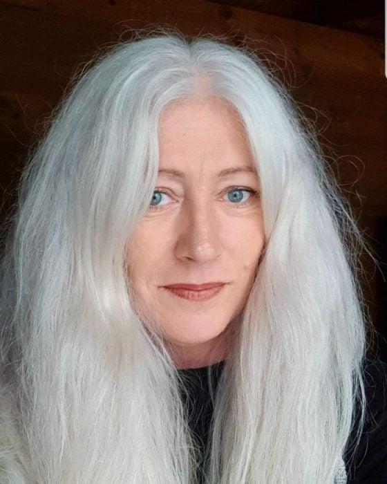Señora de ojos azues con cabello blanco, canoso esponjado