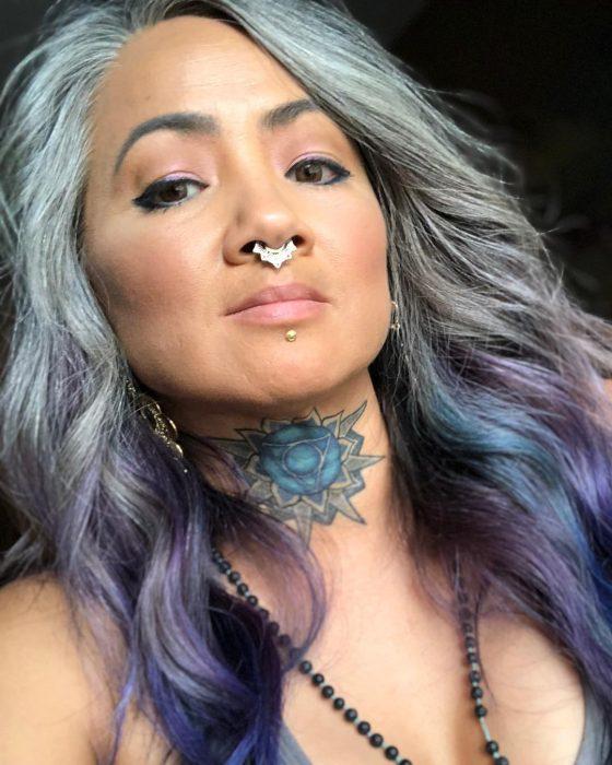 Mujer con tatuaje de flor de loto en el cuello, piercing en el septum y cabello colo gris y morado