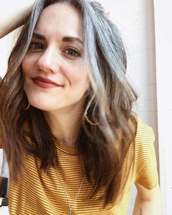 Chica de ojos verdes con cabello castaño y canas sonriendo a la cámara, blusa amarilla de líneas negras