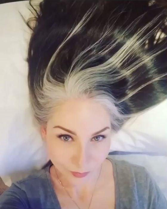 Mujer joven de ojos azules con cabello negro y canoso estilo Rogue de X-men