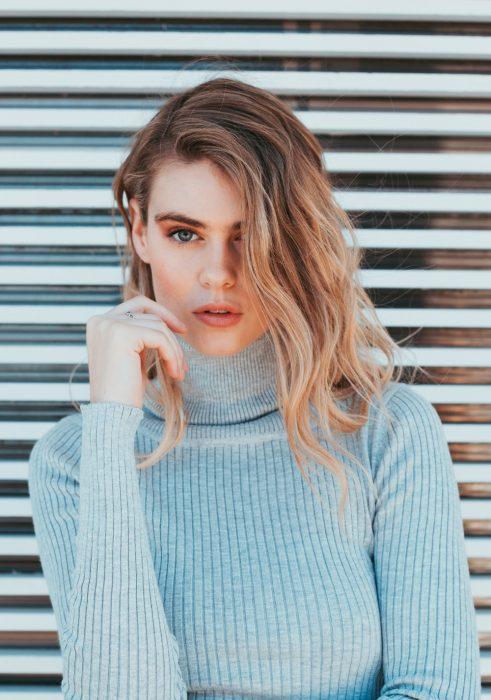 Chica recargada en una cortina de metal sosteniendo su cabello con la mano derecha