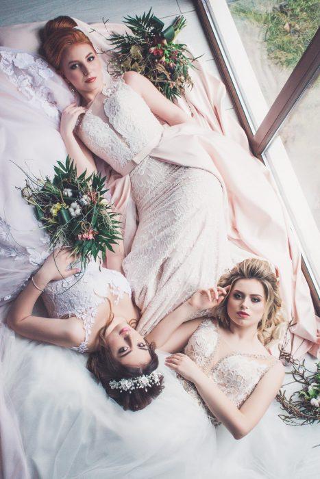 Grupo de mujeres recostadas en circulo usando vestidos de novia con encaje blanco
