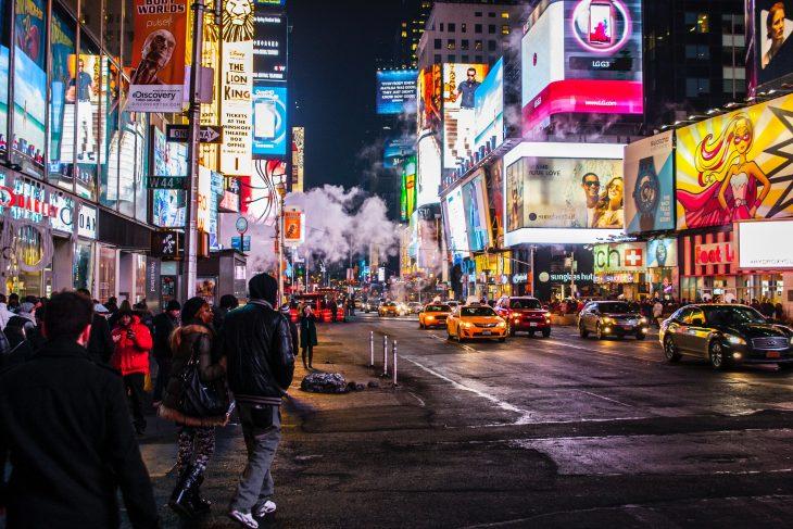 Ciudad de Nueva York llena de gente, a mitad de la noche, con las luces de los negocios encendidas