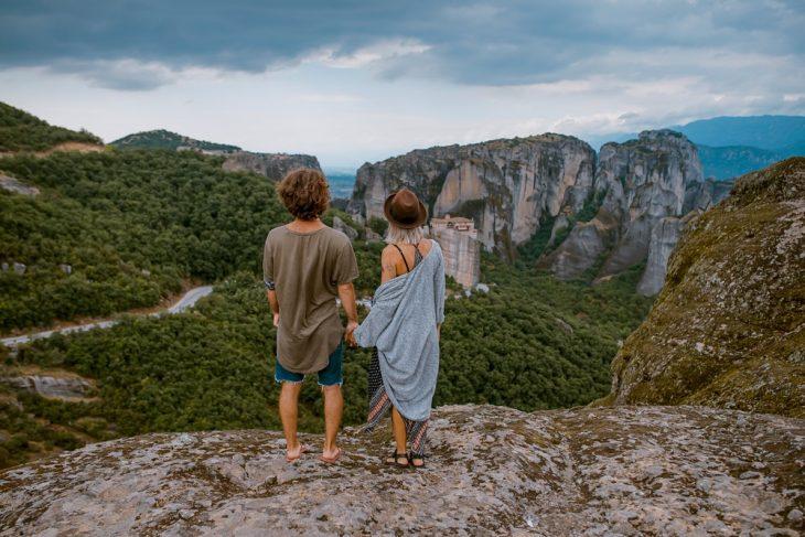 Pareja de novios tomados d elas manos sobre la cima de una montaña admirando el panorama del bosque