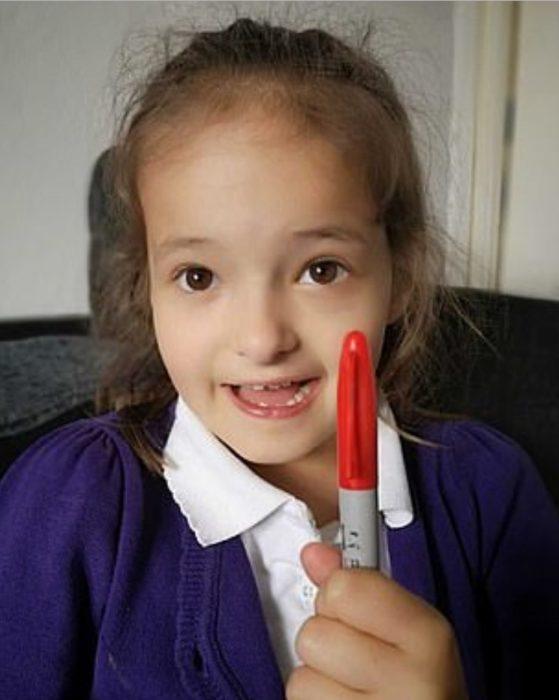 Lily Schooley, niña pequeña con uniforme escolar sosteniendo un plumón rojo