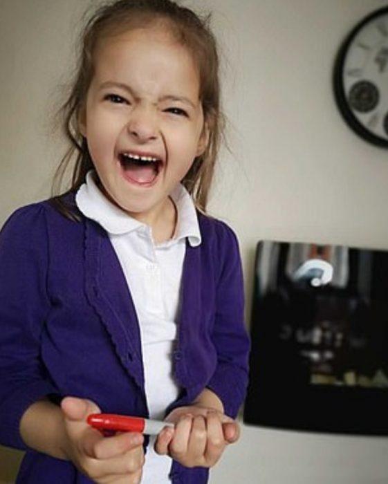 Lily Schooley, niña pequeña con uniforme escolar sosteniendo un plumón rojo y riéndose
