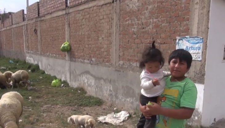 Víctor Martín Angulo Córdoba, niño de Perú hace tarea bajo un poste de luz en la calle de noche porque en su casa no hay electricidad, niño cargando a su hermana pequeña mientras cuidan a las ovejas