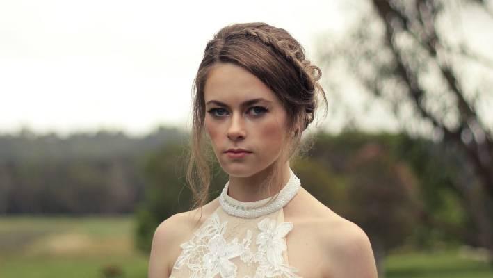 chica vestida de novia, con gesto molesto, modelando para una foto a mitad del bosque