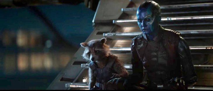 Personajes de la película Avengers: Endgame sentados en unas escaleras color plateado, tomados de la mano, Nebula, Rocket Racoon