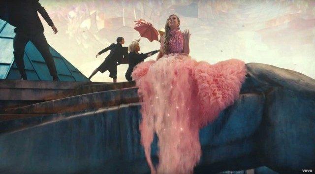 La cantante Taylor Swift luciendo un vestido rosa sobre una roca en forma de unicornio en su nuevo video musical ME
