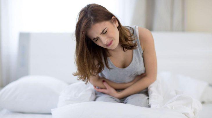 chica sentada en la orilla de una cama con dolor abdominal intenso