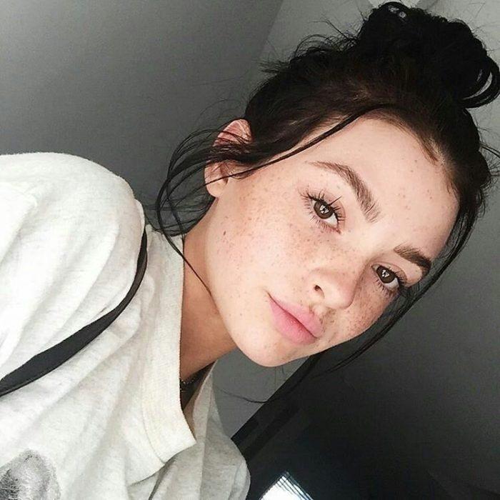 Chica con pecas en el rostros, peinado bun, sudadera blanca, sonriendo ligeramente, dentro de una habitación gris, tomando una selfie