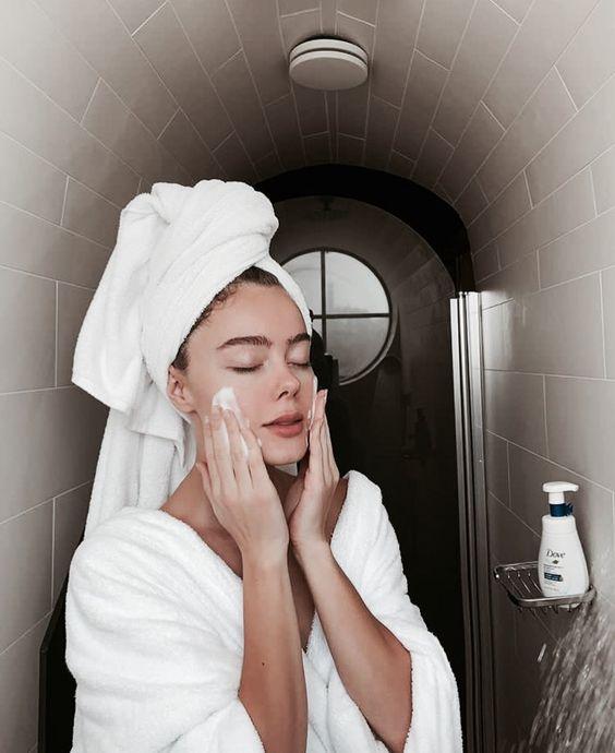Chica en bata para baño color blanco con una toalla sobre su cabello, limpiando su rostro con jabón espumoso