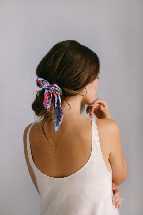 Chica de espaldas con blusa de tirantes blanca y peinada con un chongo y un pañuelo