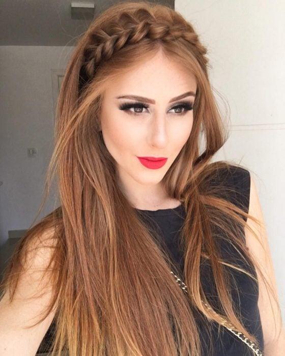 Chica con cabello pelirrojo lacio con una diadema de trenzas
