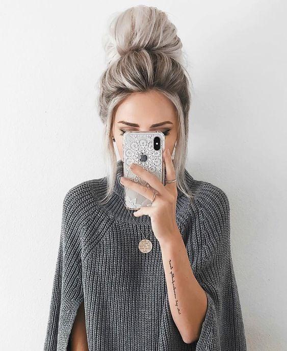 Chica tomándose una fotografía con su celular, con suéter gris y un peinado de moño alto despeinado