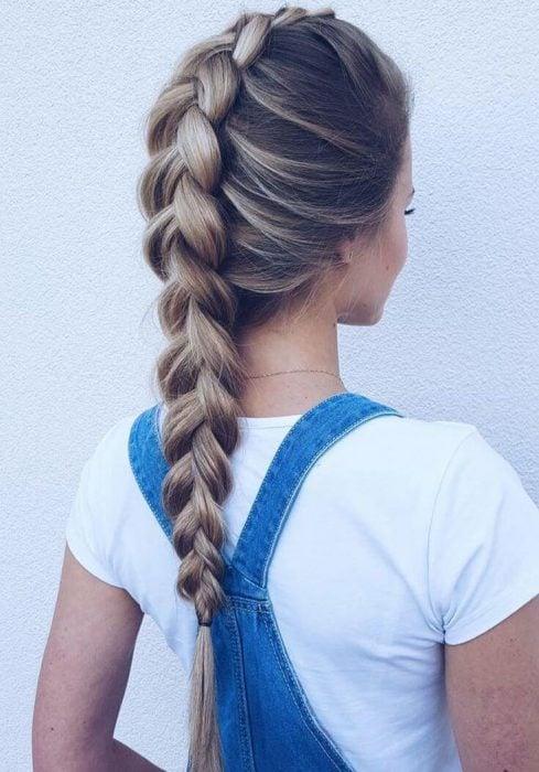 Chica de espaldas con top blanco y overol azul con una trenza invertida