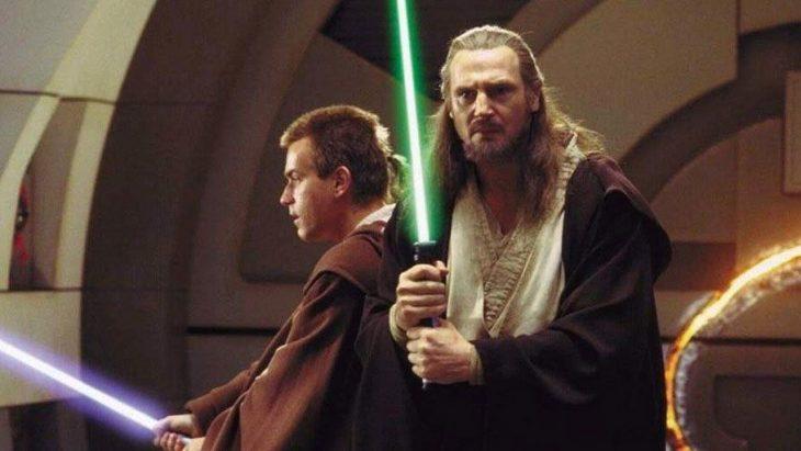 Hombres con capas de color café, sosteniendo sables de colores entre sus manos, escenas de la película Star Wars: EpisodioI, La amenaza fantasma
