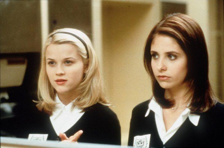 Par de amigas dentro de un baño, mirandose en el espejo mientras charlan, escena de la película Crueles intenciones, Srah Michelle Gellar, Reese Witherspoon
